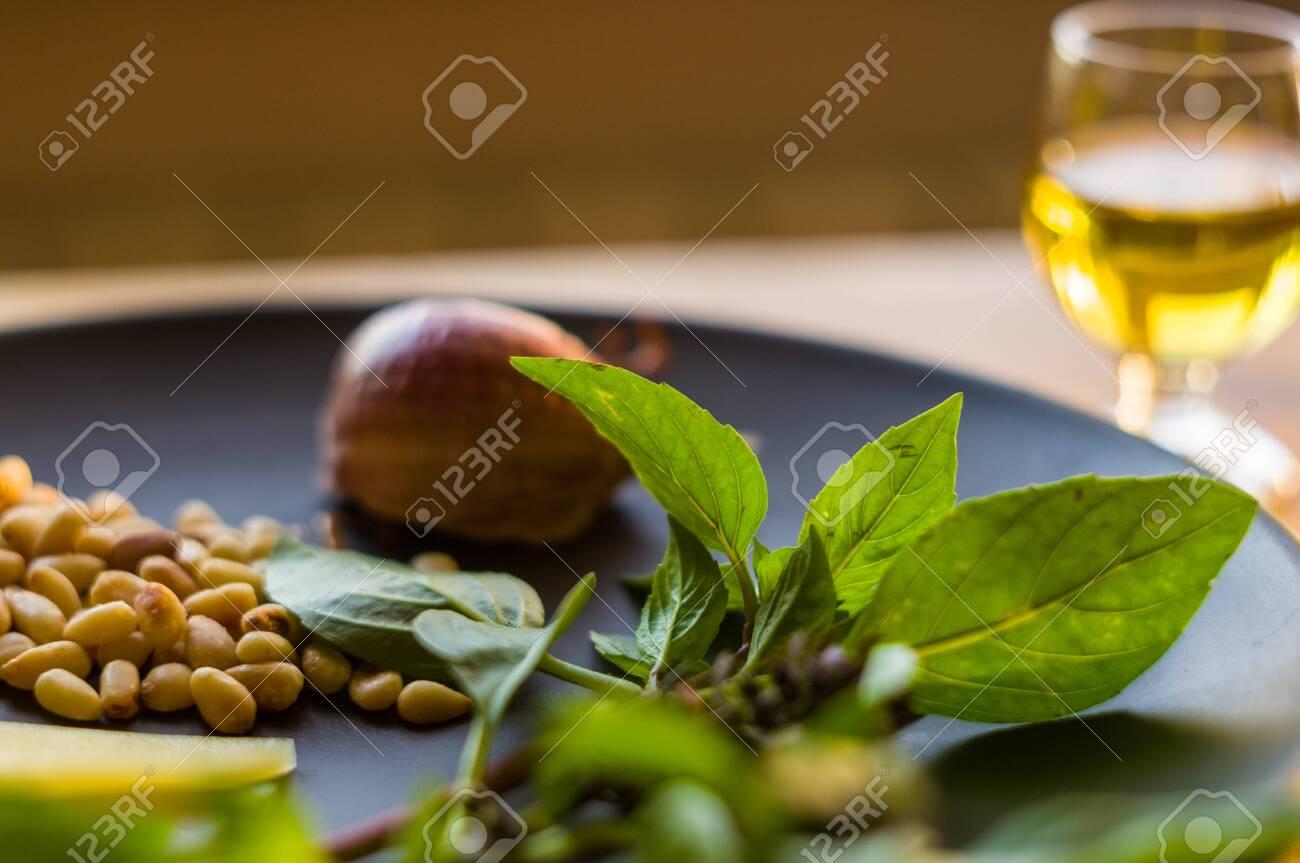 Fresh ingredients for preparing Italian pesto sauce - lemon basil sprigs, peeled seeds of cedar nuts, large garlic clove, Greek olive oil, Parmesan cheese, on a ceramic plate, in scattered sunlight - 120942906
