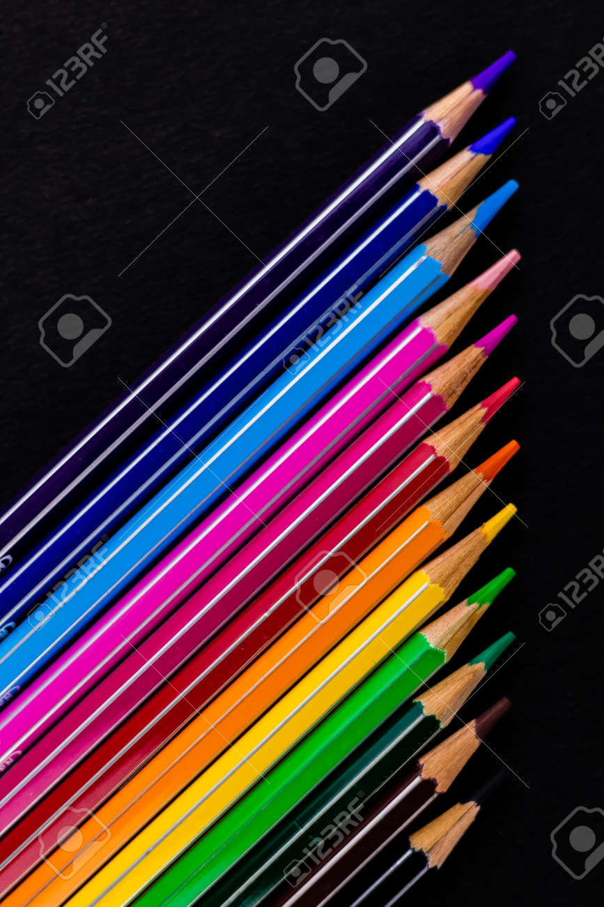 Top close up shot of beautiful color pencils arranged diagonally over a black background in Fine Art concept - 169286487