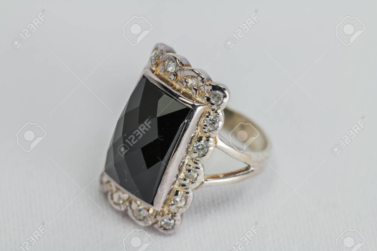 9b2a8769fe53 Anillo de plata vieja con la piedra preciosa de color negro sobre fondo  blanco satén.