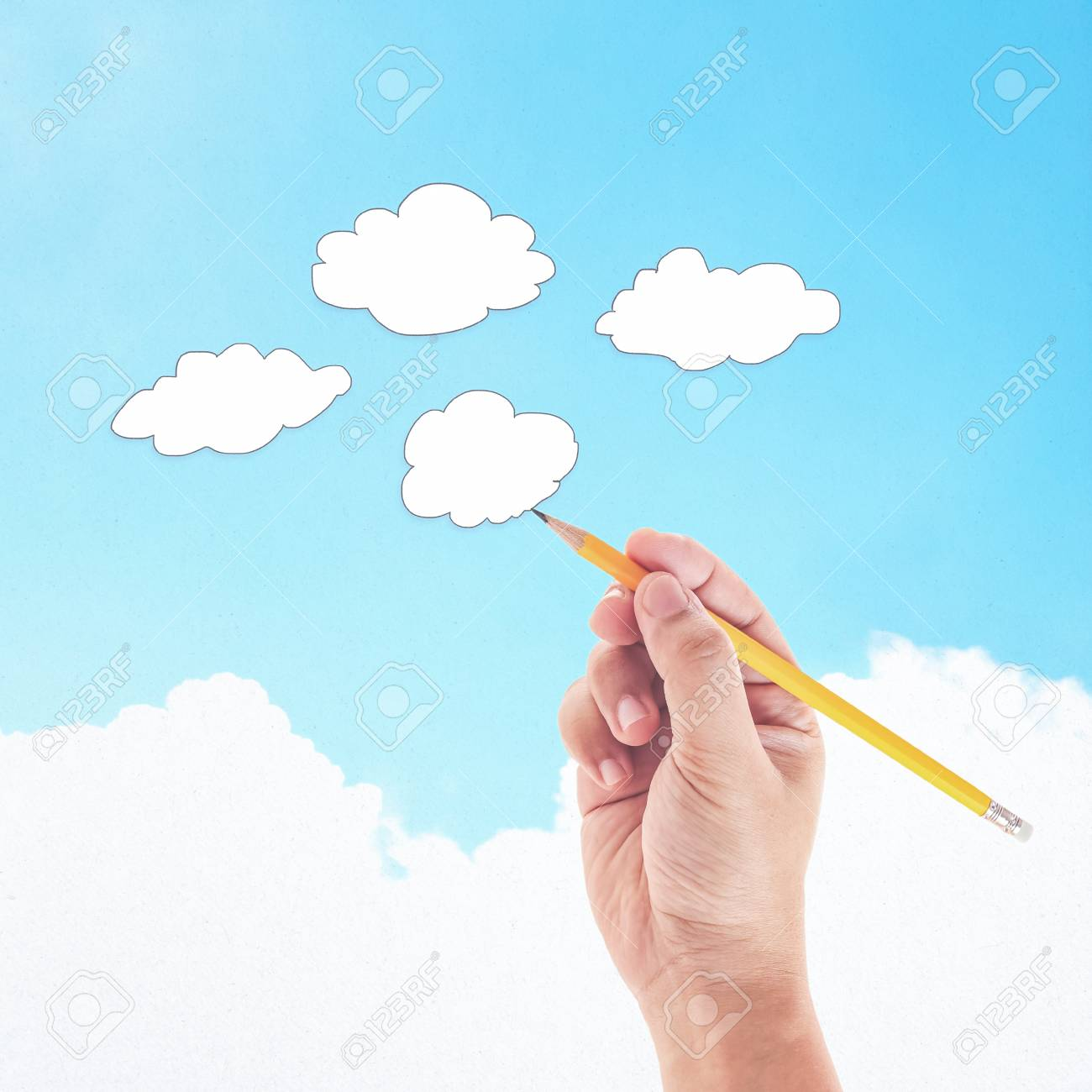 Hand with pencil drawing clouds on blue sky