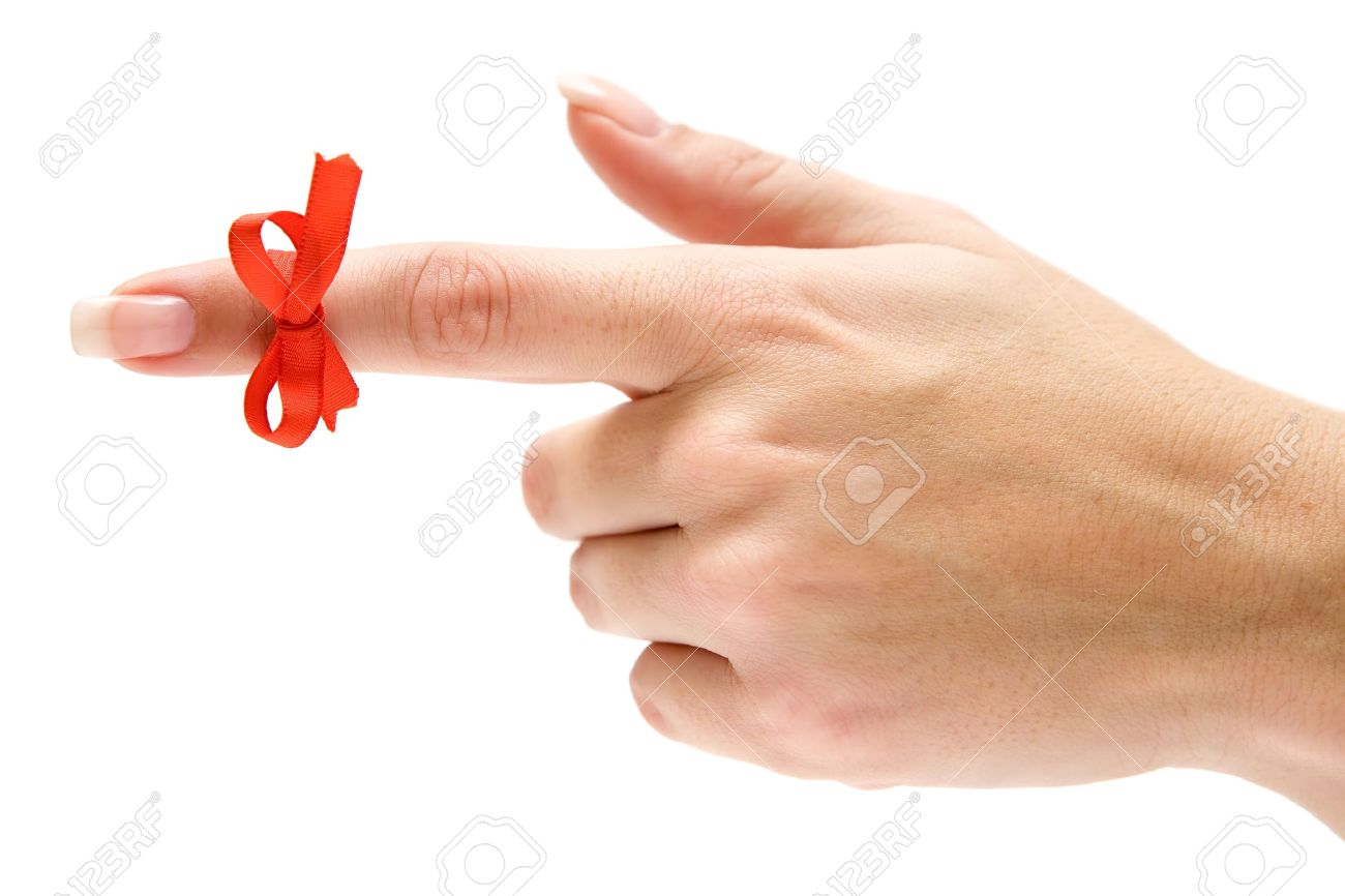 Finger with red bow pointing left. Isolated on a white background. - 2705851