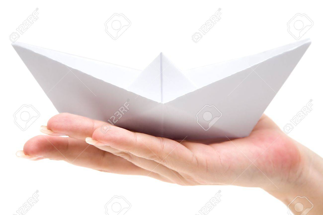 Woman holding a folded paper boat. Isolated on a white background. - 2705752