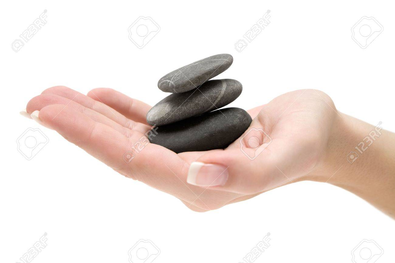 Female hand holding a stack of three dark stones. Isolated on a white background. - 2705836