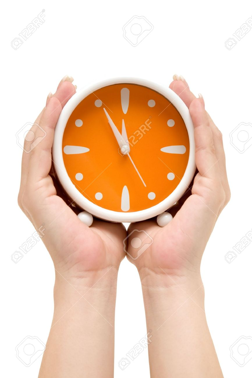 hands holding an orange alarm clock showing five minutes to midnight isolated on a