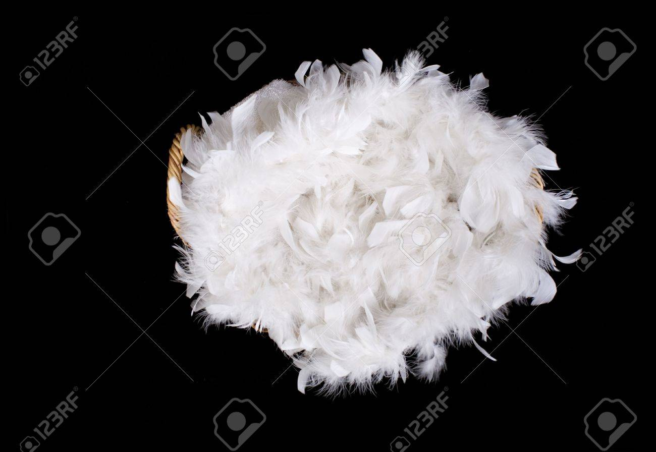 Wicker Basket Filled With Soft White Feathers Isolated On Black
