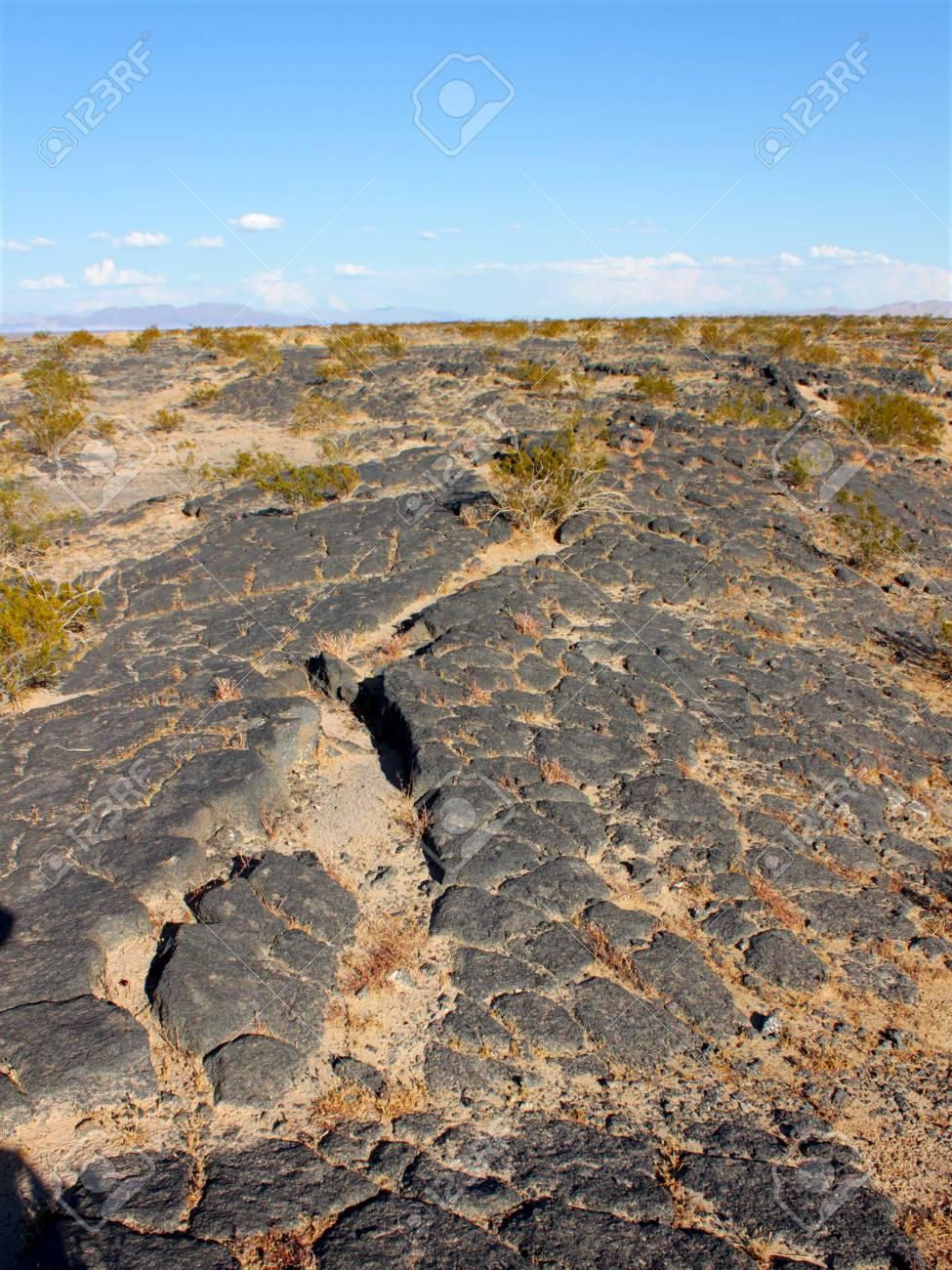 Volcanic rock scatters the desert around Amboy Crater National Natural Landmark in California Stock Photo - 9896719