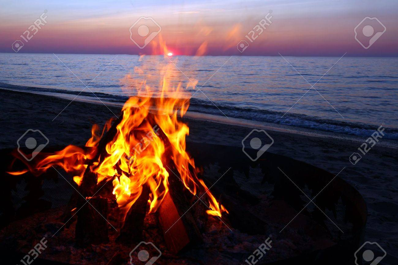 Blazing campfire at sunset along the beautiful beach of Lake Superior in northern Michigan Stock Photo - 10500748