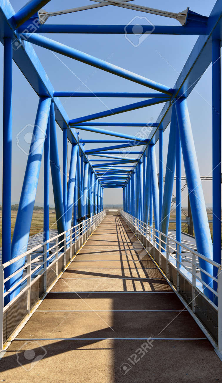 A vertical shot of a bridge with blue poles on a sunny day - 156717716
