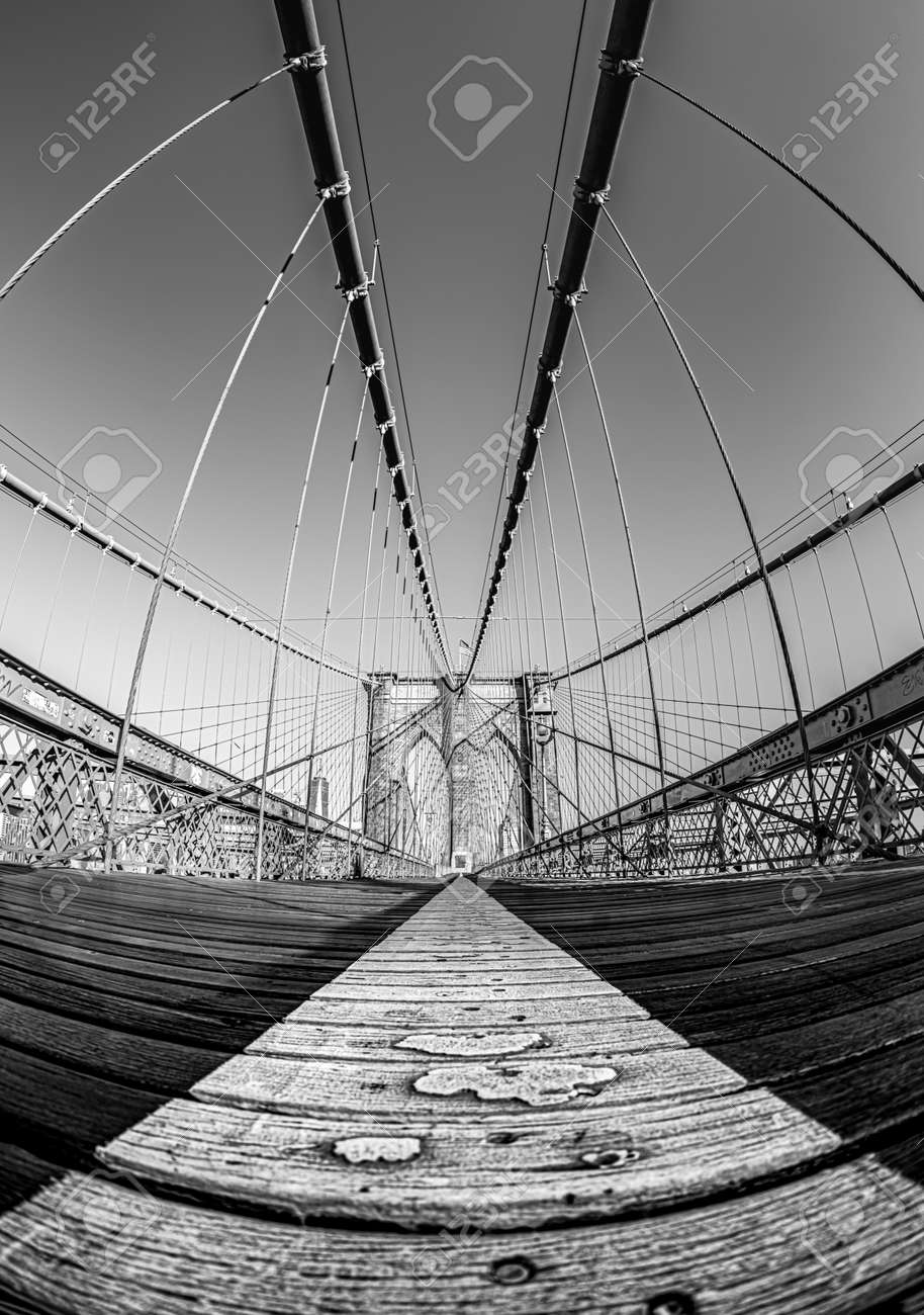 A vertical greyscale shot of a suspension bridge under the clear sky - 154973858