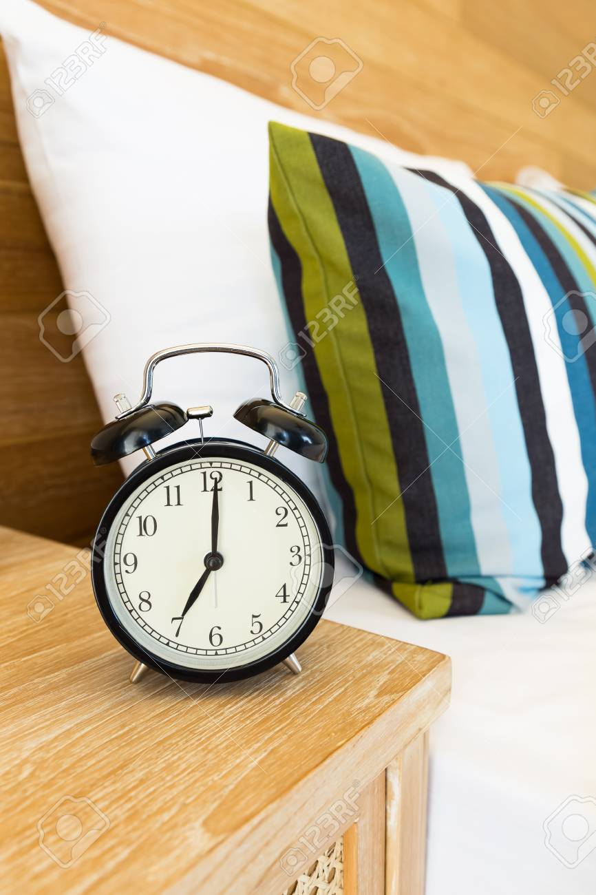 Stock Photo   Vintage Retro Alarm Clock On Bed Side Table At 7 Ou0027clock