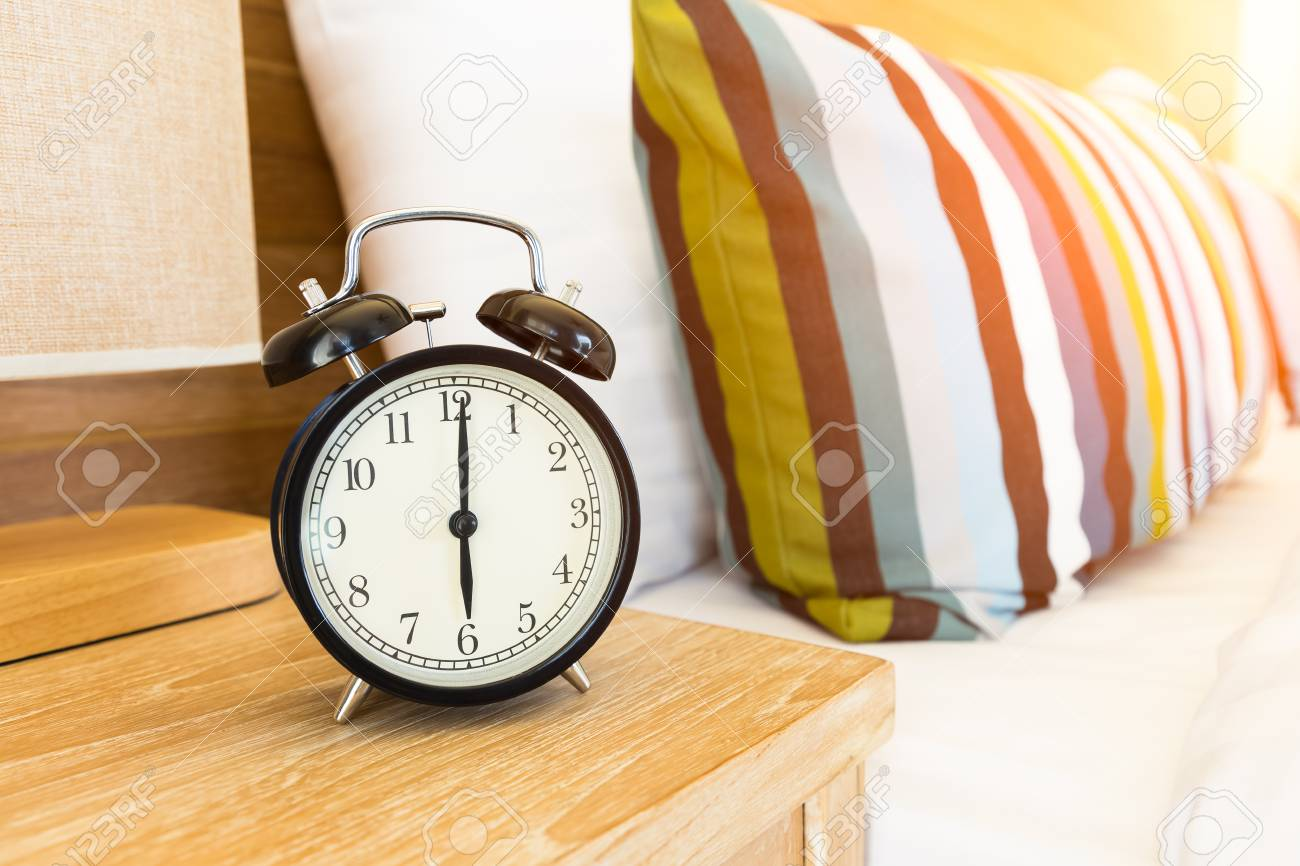 Stock Photo   Vintage Retro Alarm Clock On Bed Side Table At 6 Ou0027clock