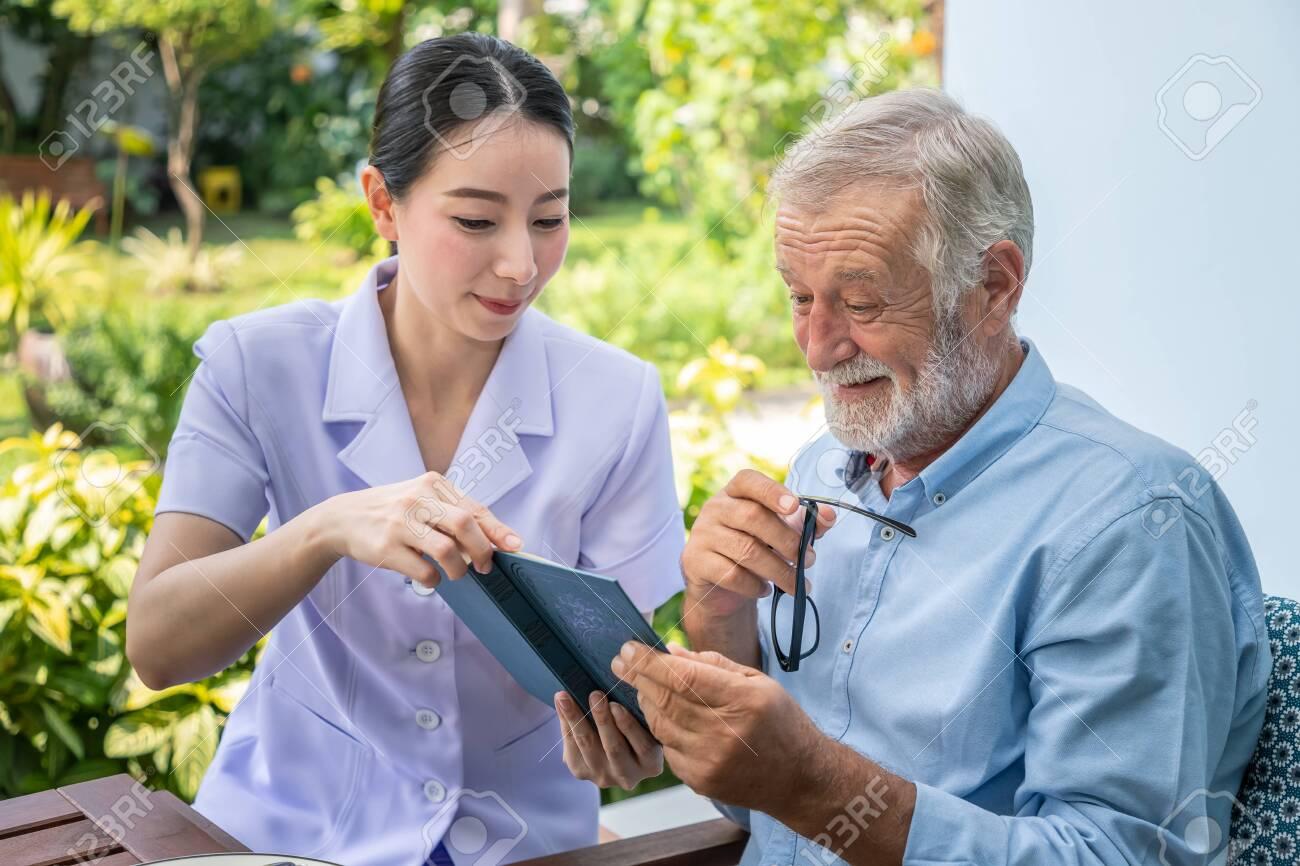Senior elderly man reading book with nurse during breakfast in garden at nursing home - 128570870