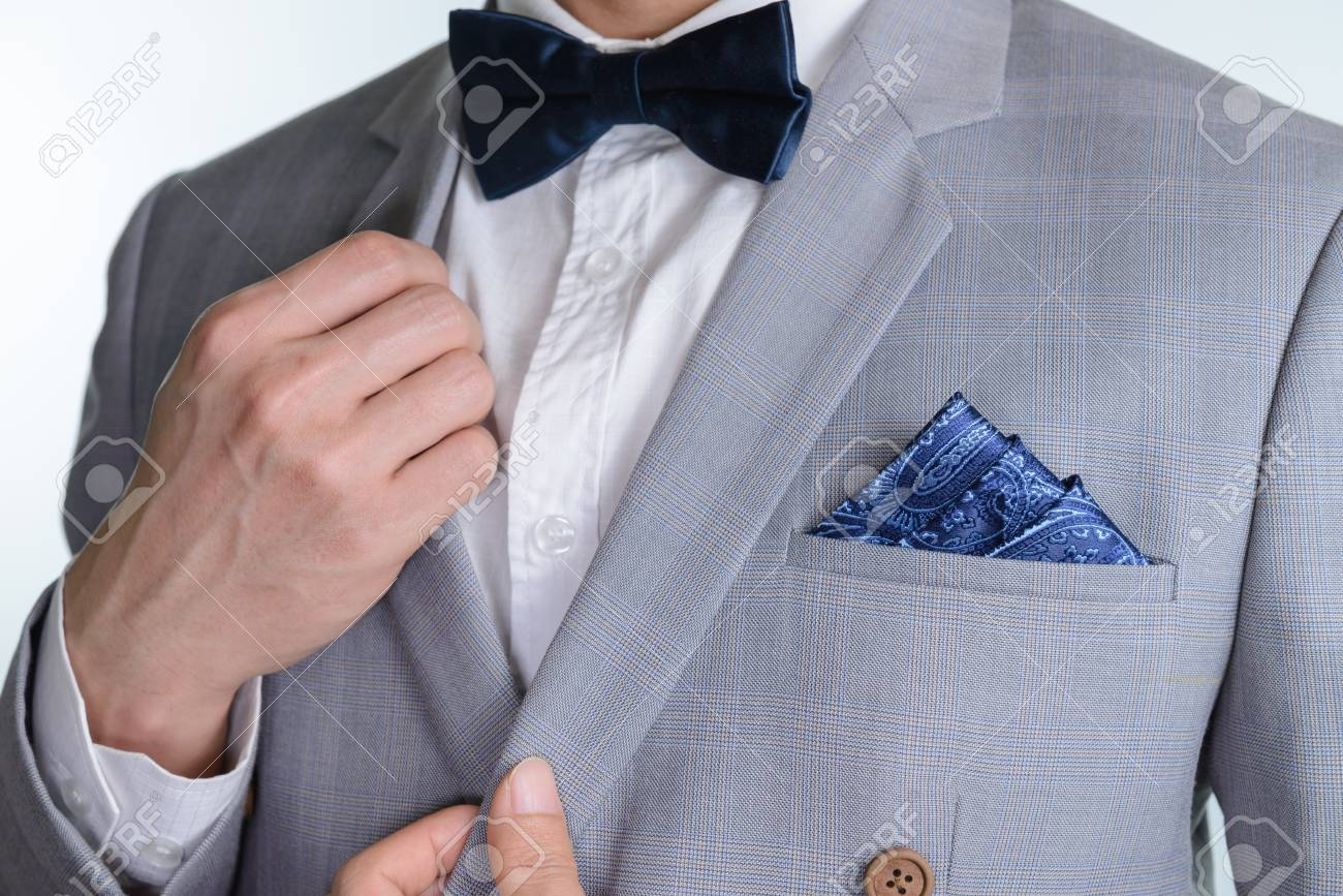Man in grey suit, plaid texture, blue bowtie and pocket square,..