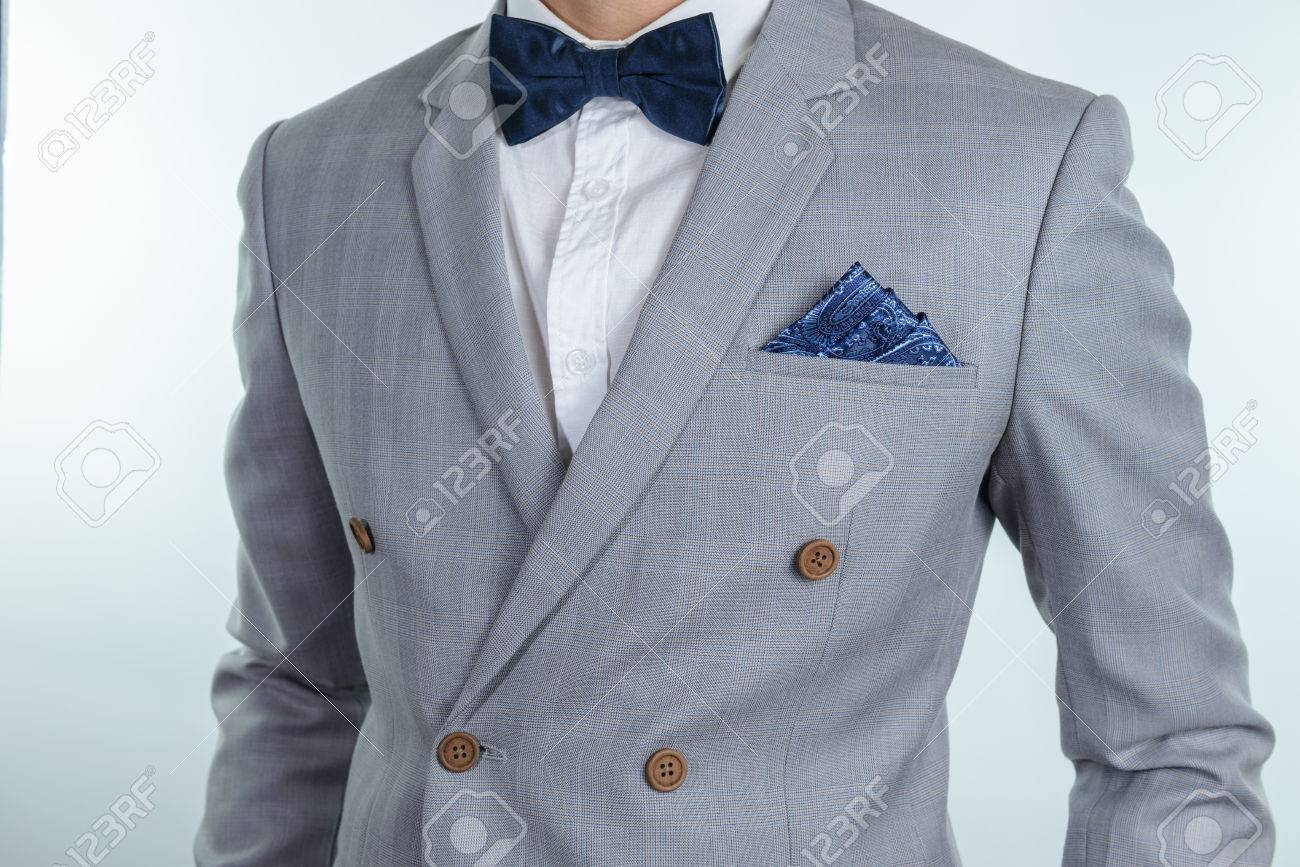 34f96385f4b9 Man in grey suit, plaid texture, blue bowtie and pocket square, close up