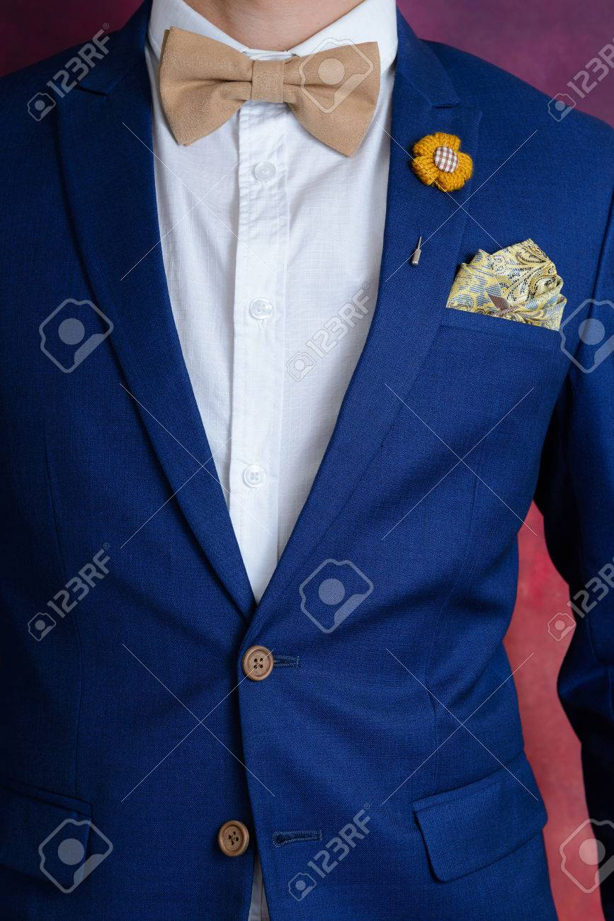6b70b9730f27 Man in blue suit with brown bow tie, flower brooch, and classic texture  pocket