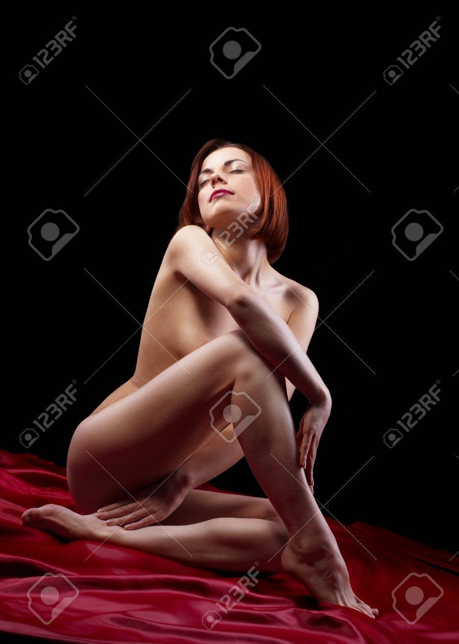 Young beauty naked woman sit on red in dark Stock Photo - 9069934