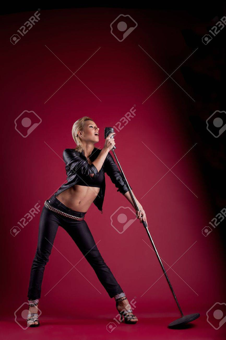 Beauty blond woman sing in black leather on red with mic like rock star Stock Photo - 11865732