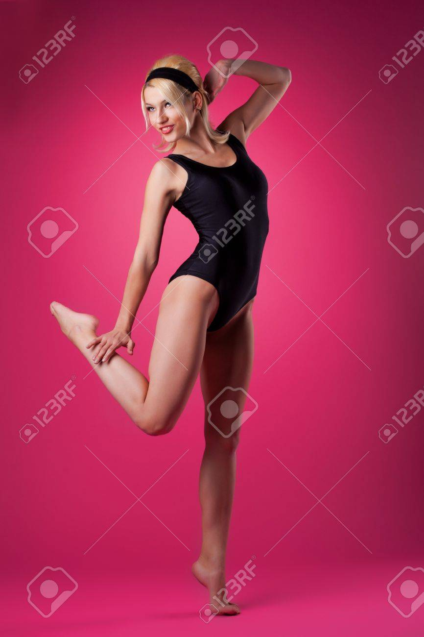 Young sport woman dance in pin up style black suit on pink stock photo young sport woman dance in pin up style black suit on pink background thecheapjerseys Gallery