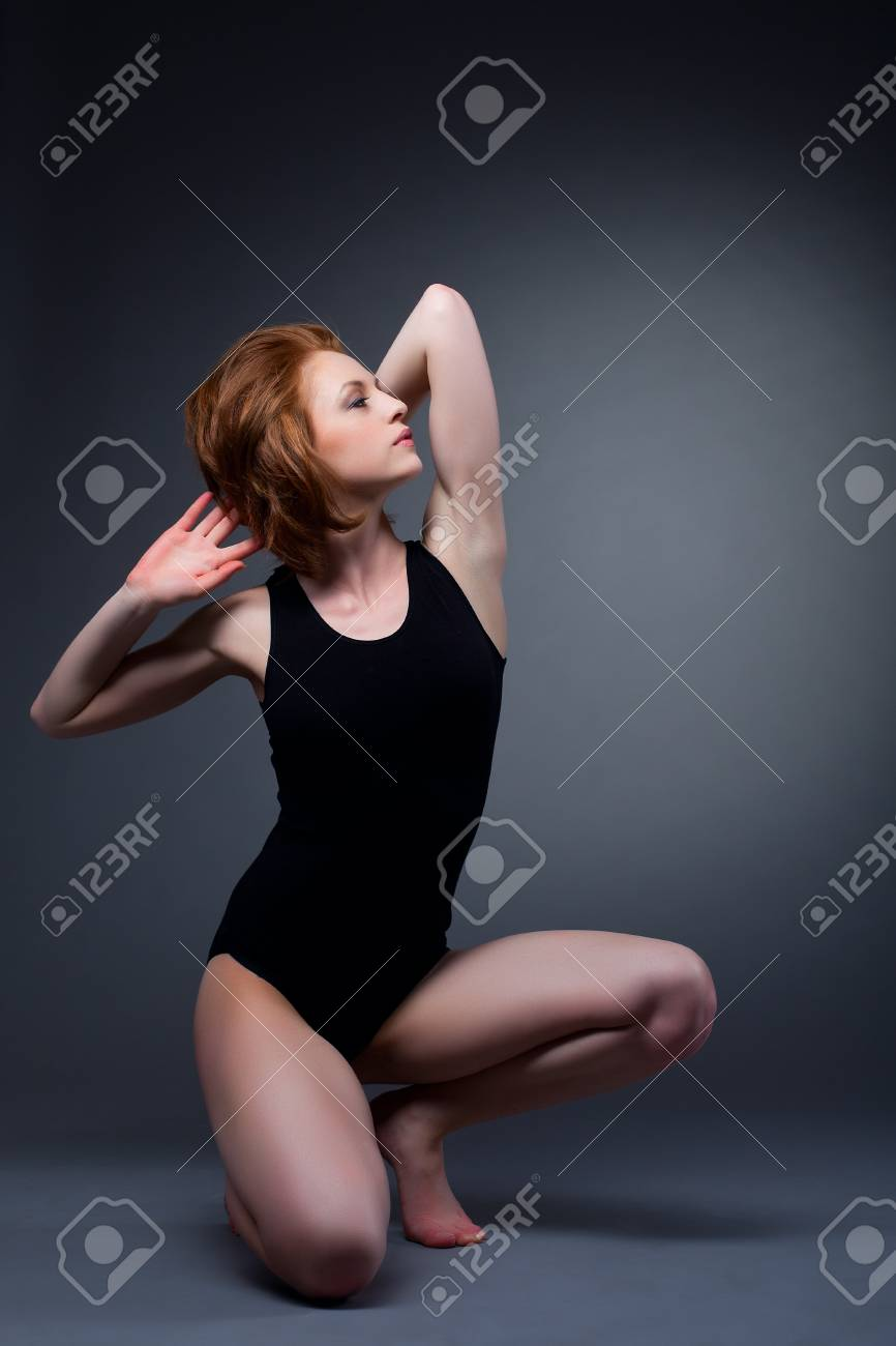 Athletic sexy woman posing on dark background in sport wear Stock Photo - 13167236