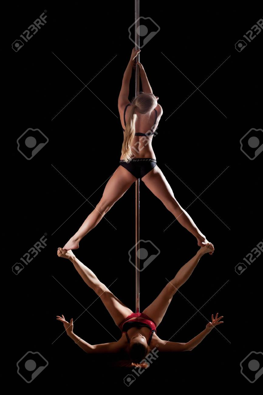 two women show high gymnastic level during pole dance isolated stock