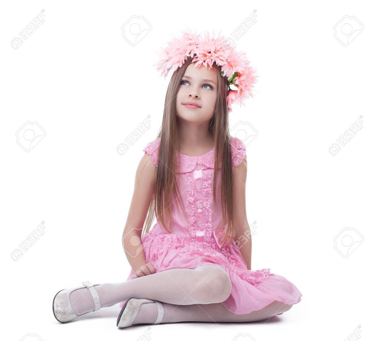 32ac3cd84ea9 Little girl in pink dress and wreath sitting on floor Isolated on white  Stock Photo -