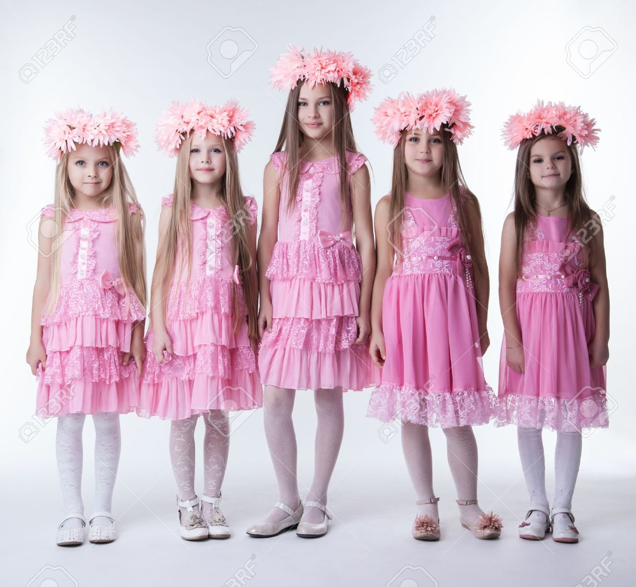 Full length portrait of five little girls in pink dresses and wreaths - 16383251