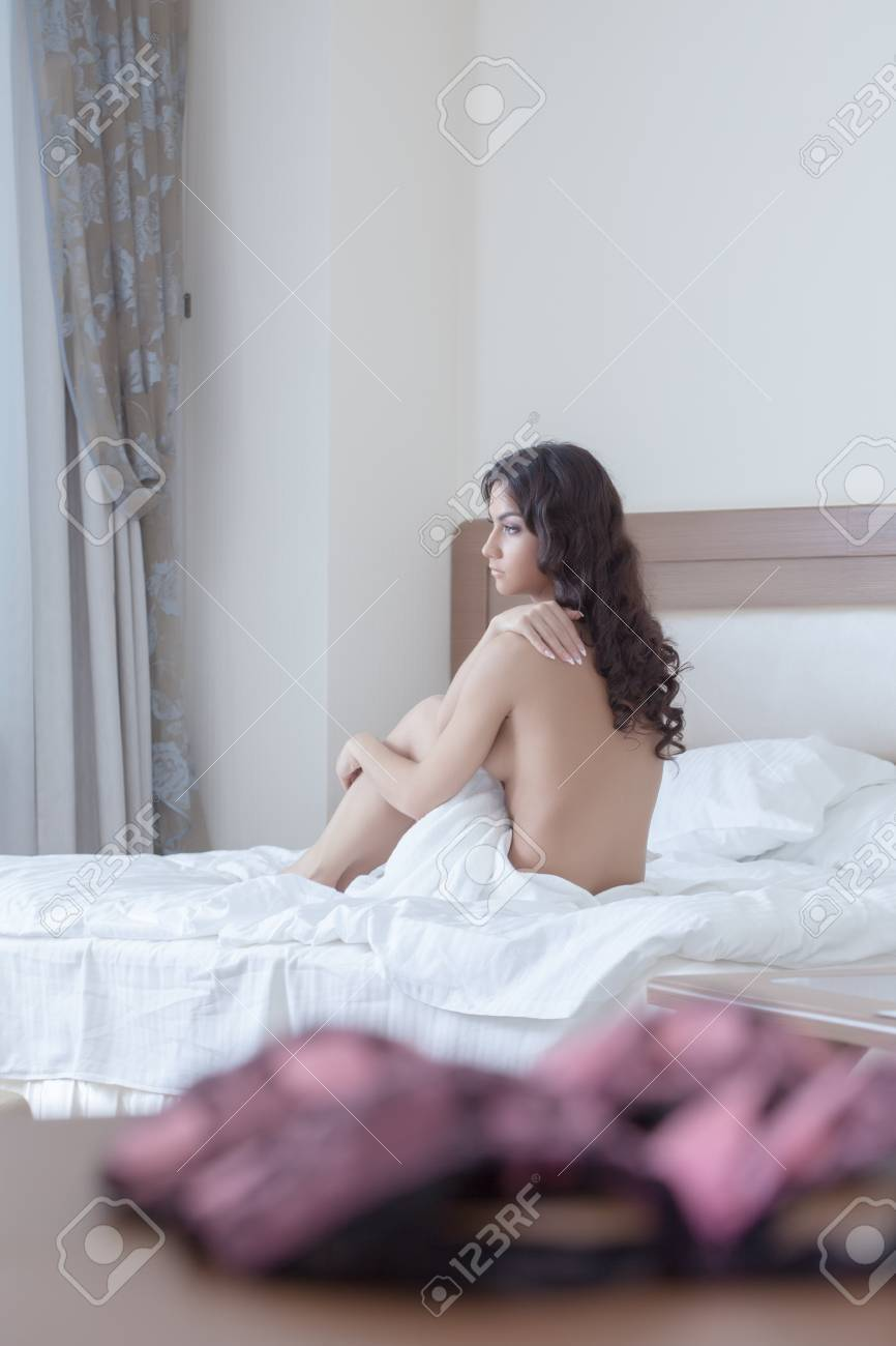 Sexy brunette young woman sitting on bed Stock Photo - 16987938