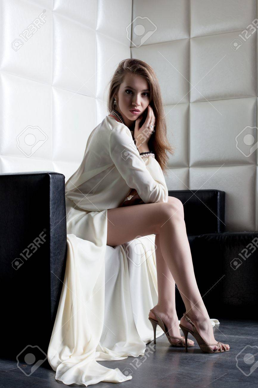 Full length portrait of beautiful woman in white dress sitting on sofa Stock Photo - 17255337
