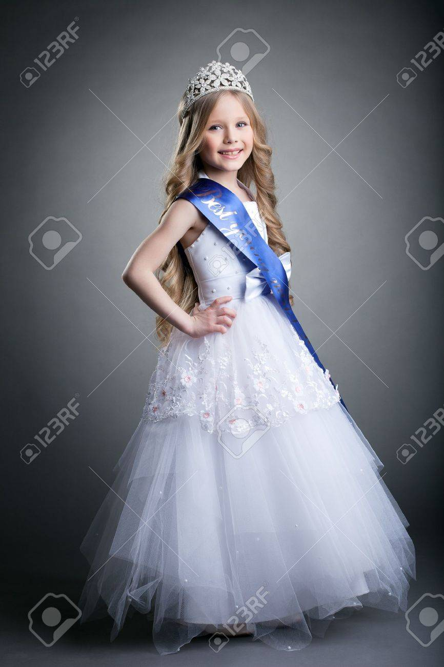 Full length portrait of pretty little girl in tiara and long white dress - 17533736
