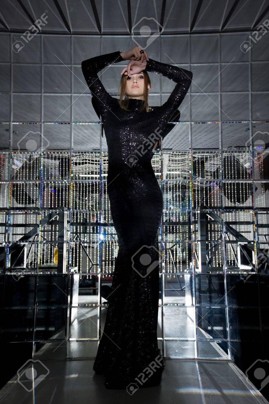 Full length portrait of Beautiful woman in long black dress mirror room of  fashion night. Full Mirror Room