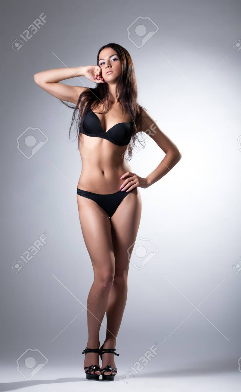 Young slim model posing in black lingerie, on gray background Stock Photo - 19356691