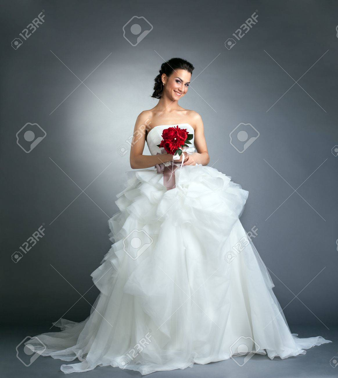 Charming bride with bouquet posing in studio, on gray background - 19564064