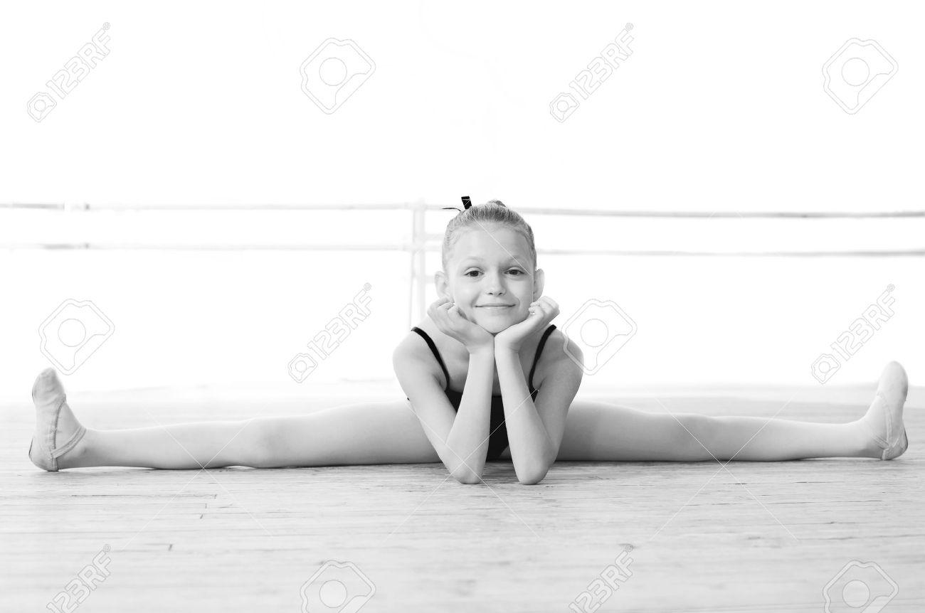 Black and white photo Smiling ballerina doing gymnastic split - 30049143