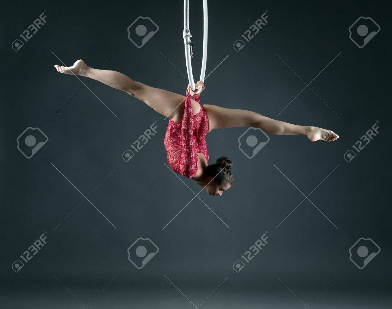 Flexible girl performs trick with hanging hoop, on gray background - 41653854