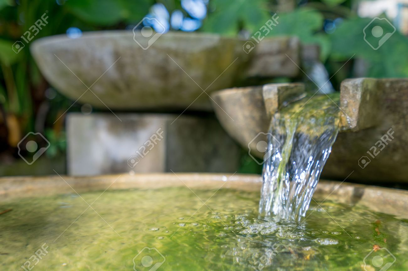 Tropical garden. Image of stone bowl with water flowing. Thailand - 51917763