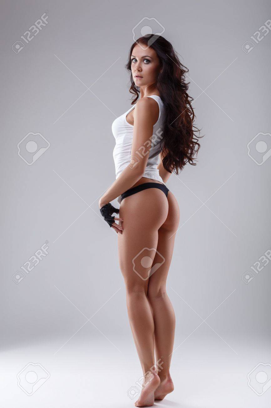 Stock Photo - Studio photo of sporty brunette with nice ass, on gray  background