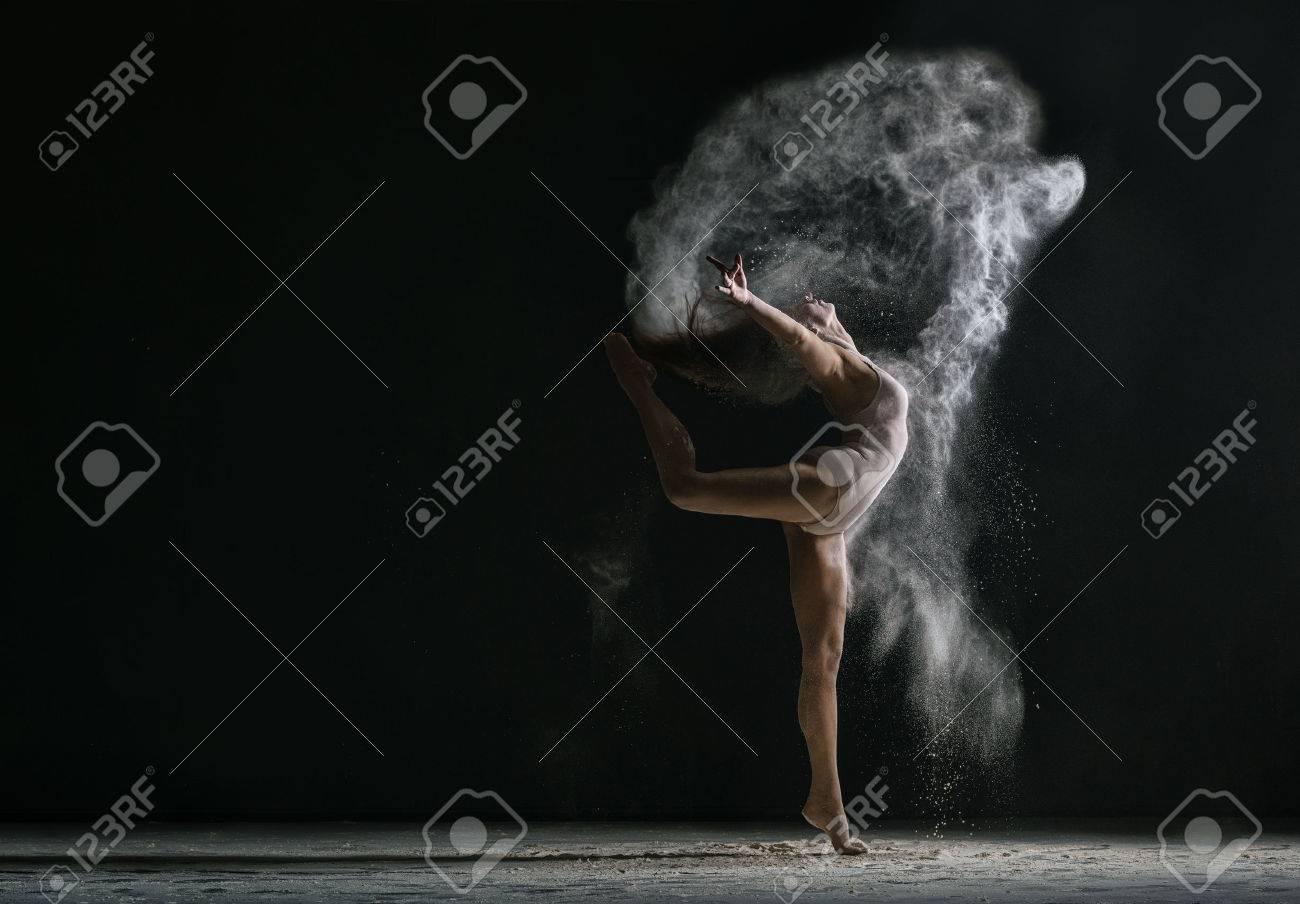Concept. Flexible woman dancing in cloud of dust - 60617065
