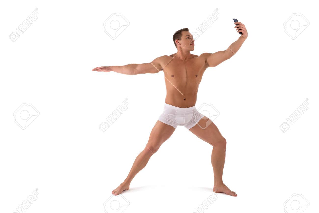 Muscular shirtless man in yoga pose taking selfie on smartphone - 167968483
