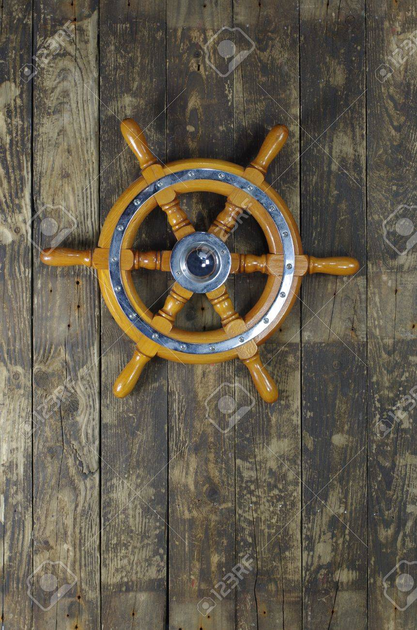 steering wheel of sailing-ship on a board background - 16025920