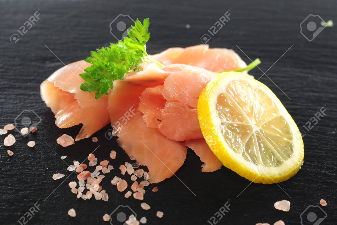 slices of smoked salmon with dill black plate background - 142680773