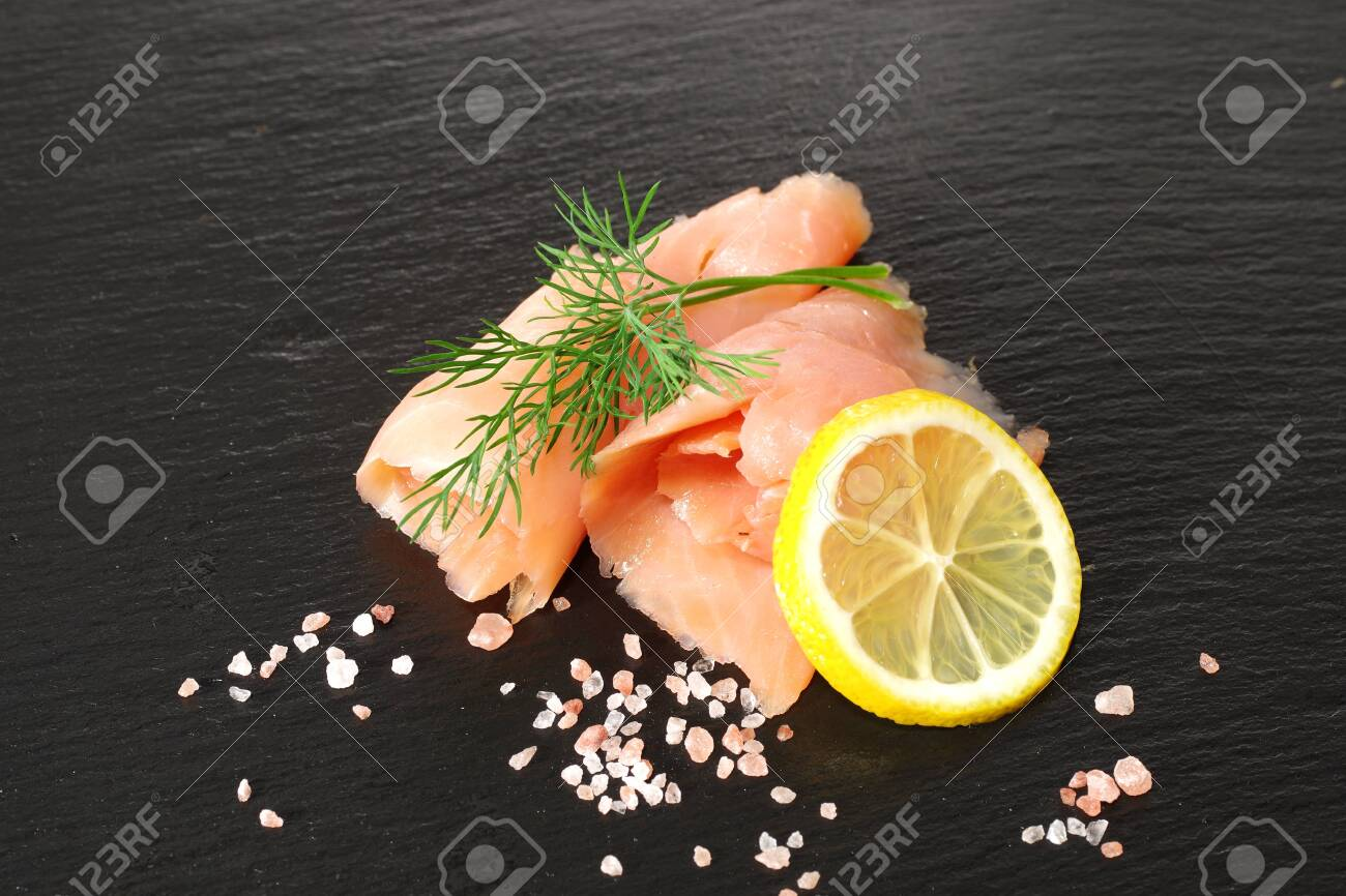 slices of smoked salmon with dill black plate background - 142680521