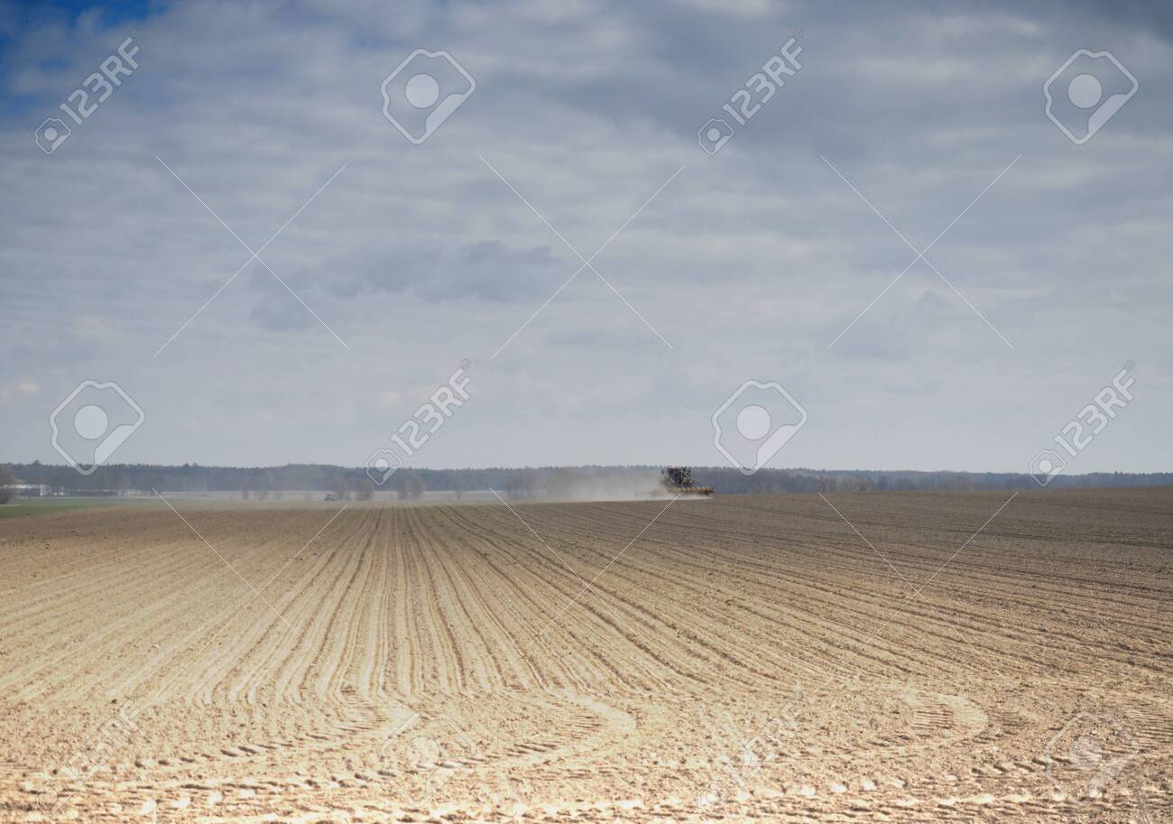 tractor driving across the field on blue sky background - 146682769