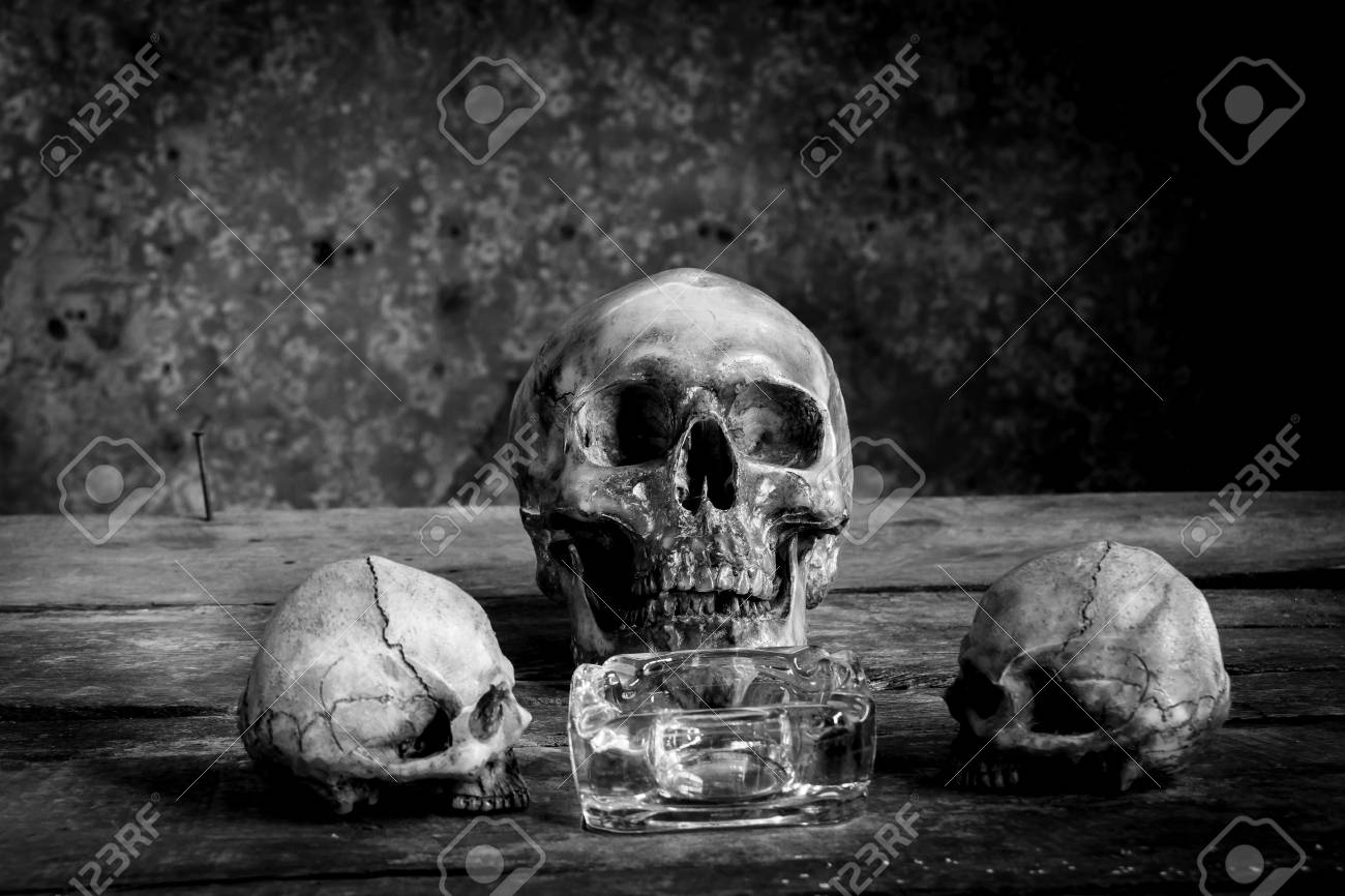 Still life black and white photography with human skulls on wood table stock photo 62190182