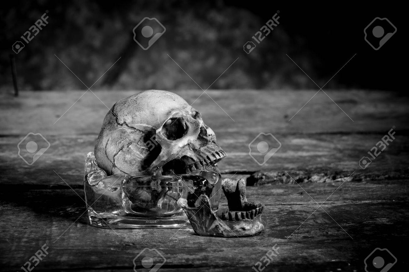 Still life black and white photography with human skulls on wood table stock photo 62190191