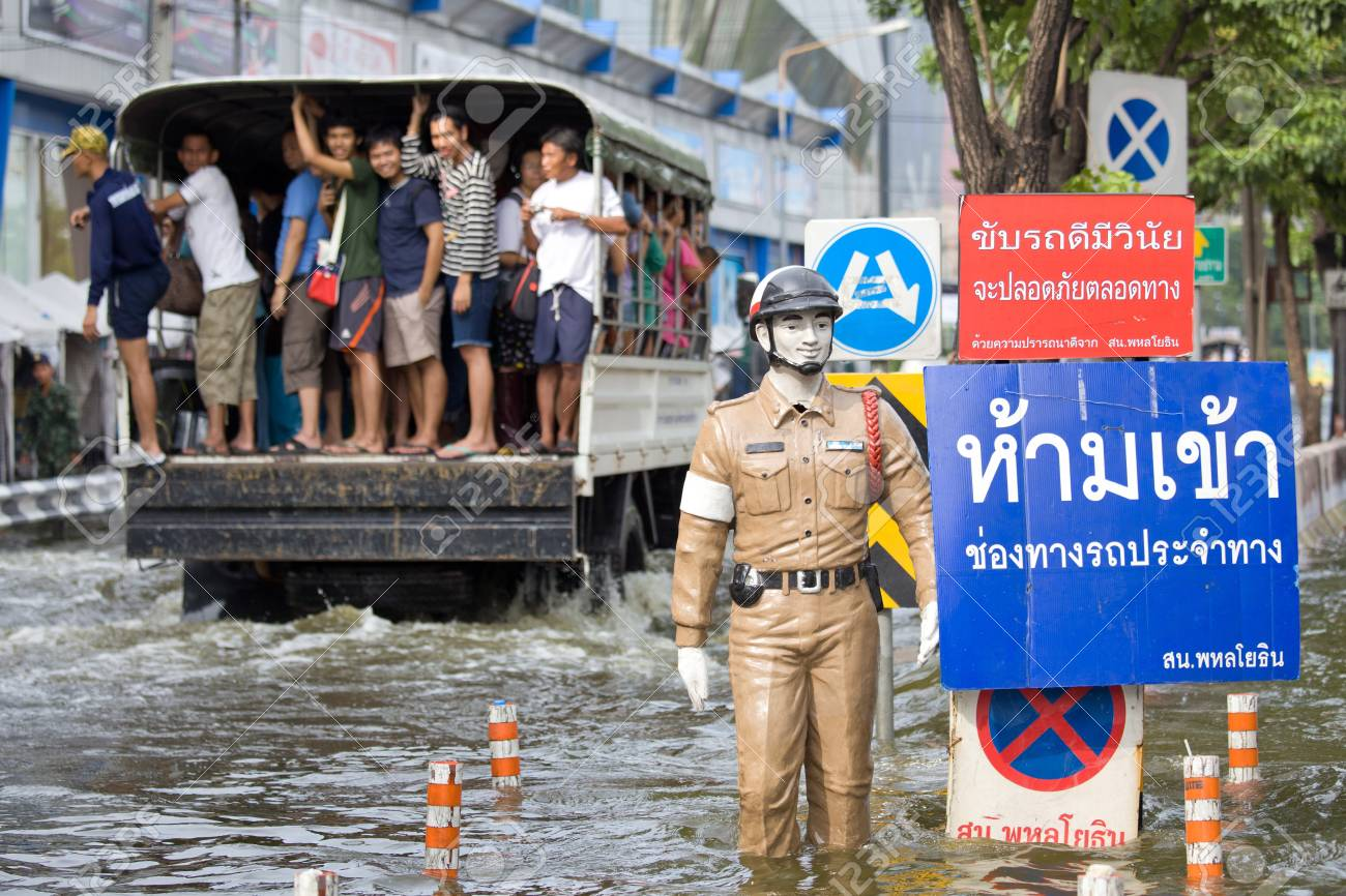 BANGKOK, THAILAND - NOVEMBER 5, 2011 : Police puppet standing on flood hits Central of Thailand, higher water levels expected, cars navigating through the flood on November 5,2011 Bangkok, Thailand. Stock Photo - 11109383