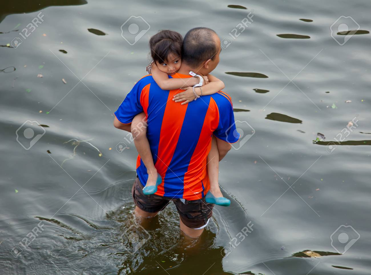 BANGKOK, THAILAND - NOVEMBER 5, 2011 : An unidentified man rescues girl during the worst flooding in decades on November 5,2011 Bangkok, Thailand. Stock Photo - 11116792