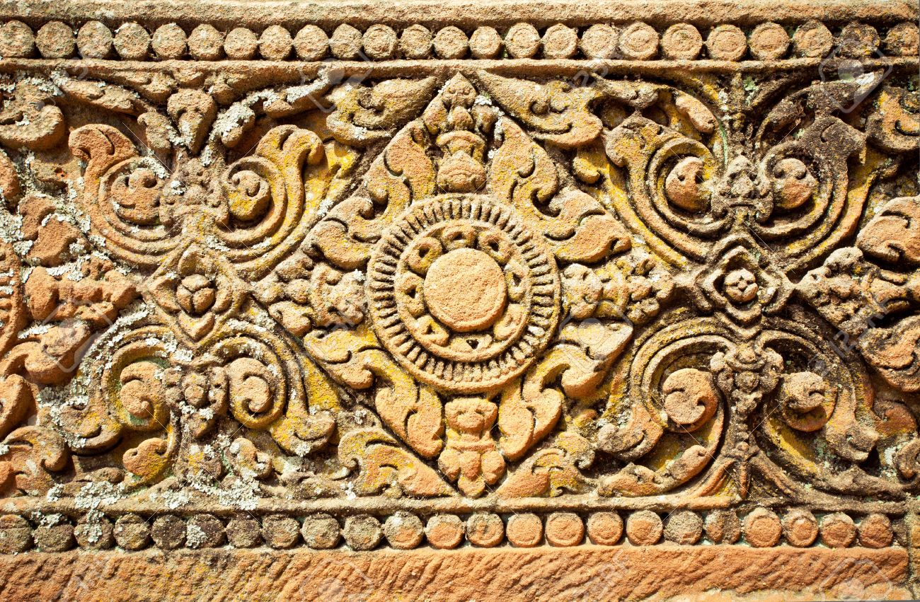 Old stone carvings on the wall temple in thailand stock photo