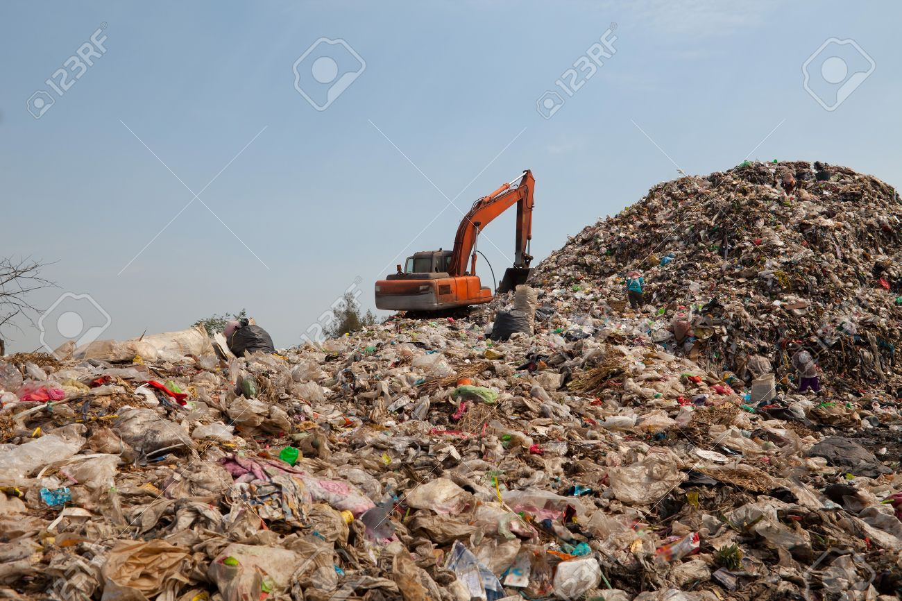 Backhoe moves trash in a landfill site, pollution, Global warming - 18236158