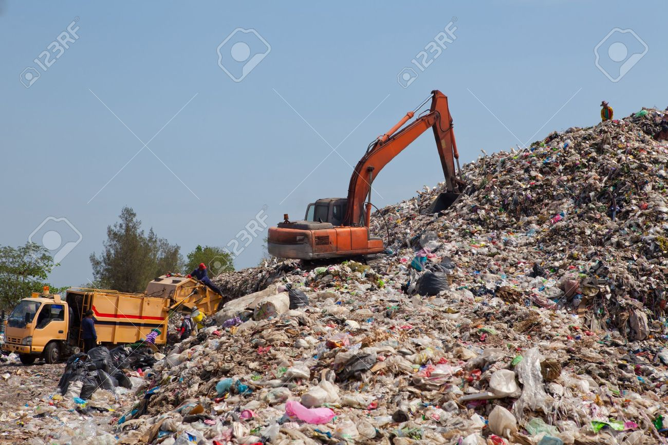 Backhoe moves trash in a landfill site, pollution, Global warming - 18269093