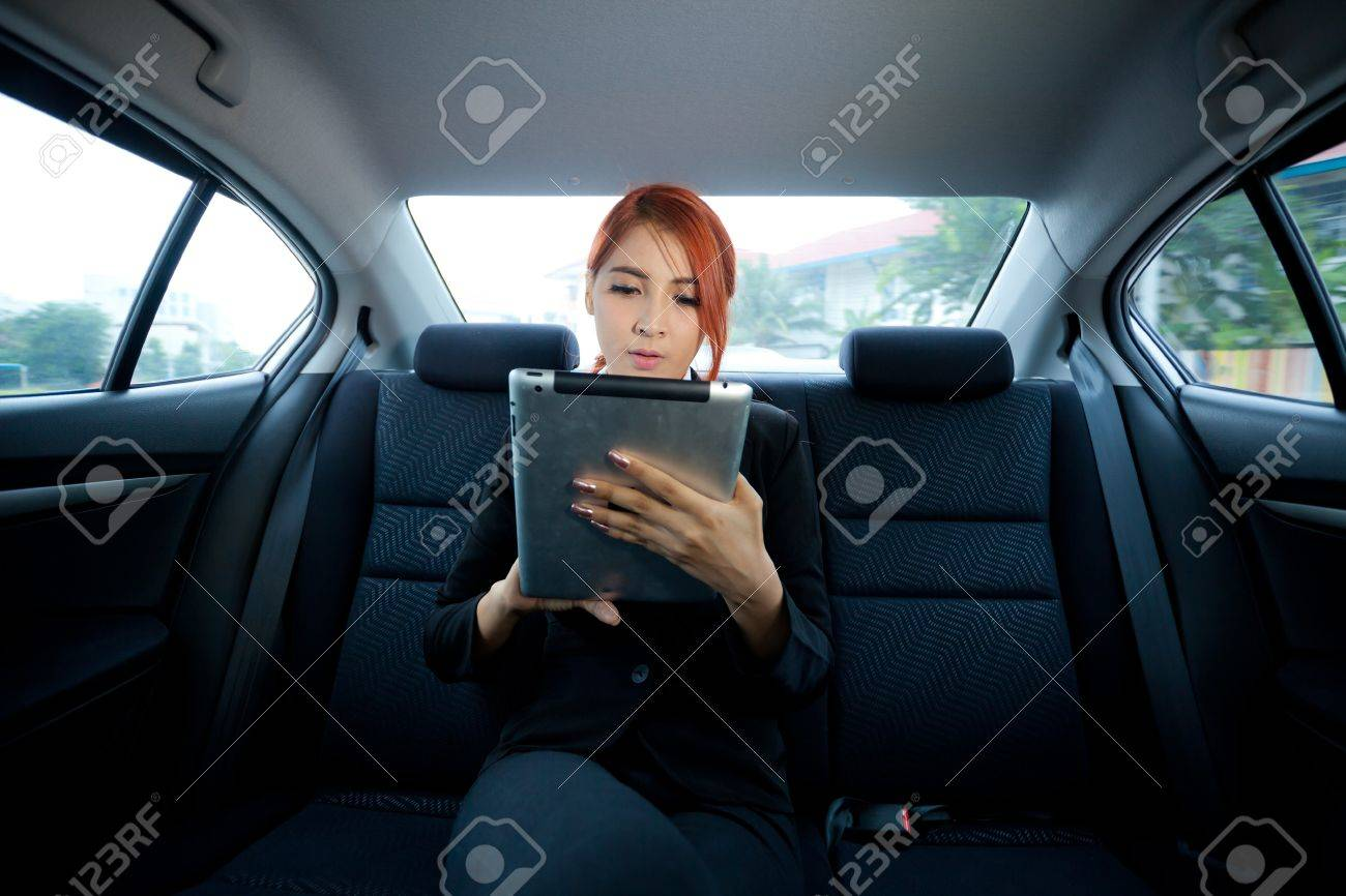 Young business asian woman inside her car using a tablet - 23955826